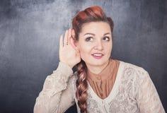 La femme drôle avec la grande oreille écoutent clandestinement image libre de droits