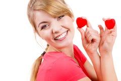 La femme drôle tient le symbole rouge d'amour de coeurs Photo stock