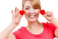 La femme drôle tient le symbole rouge d'amour de coeurs Image stock