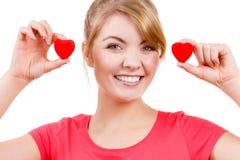 La femme drôle tient le symbole rouge d'amour de coeurs Image libre de droits