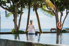 La femme du dos dans le costume de sport s'assied dans la pose de lotus, méditant au bord de la piscine sur la côte de l'océan da photographie stock libre de droits