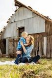 La femme embrasse son fils avec le fond de grange Photographie stock libre de droits