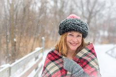 La femme a empaqueté dans l'extérieur de chapeau et d'écharpe tout en neigeant image libre de droits