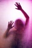 La femme emprisonnée, dos a allumé la silhouette des mains derrière le verre mat images stock