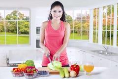 La femme en bonne santé coupe les légumes frais et le fruit Photo libre de droits