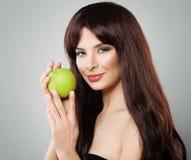 La femme en bonne santé souriant et tenant Apple vert portent des fruits photo stock
