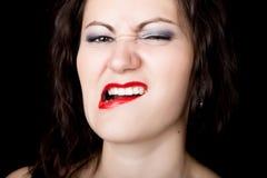 La femme en gros plan regarde directement dans l'appareil-photo sur un fond noir exprime différentes émotions, montrant des dents image libre de droits