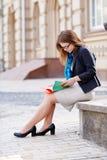 La femme en verres s'assied sur un banc en pierre et lire un livre Photographie stock