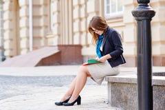 La femme en verres s'assied sur un banc en pierre et lire un livre Images stock
