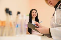La femme enceinte écoutent son docteur dans la clinique photographie stock libre de droits