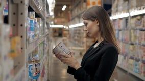 La femme enceinte achète les couches-culottes au supermarché, portrait de jeune mère heureuse dans la boutique Photo libre de droits