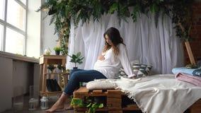 La femme enceinte attirante s'assied dans le lit et tient son ventre photos libres de droits