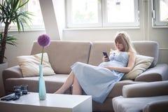 La femme enceinte avec le smartphone s'asseyent dans le sofa à la maison Photos stock