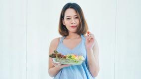 La femme enceinte d'Asiatique mange de la salade photographie stock libre de droits