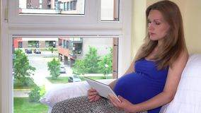 La femme enceinte dans la chemise bleue utilise le comprimé à la maison se reposant près de la fenêtre banque de vidéos