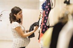 La femme enceinte dans des vêtements stockent regarder quelques vêtements Images libres de droits