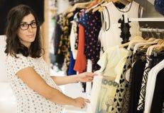 La femme enceinte dans des vêtements stockent regarder quelques vêtements Photo libre de droits