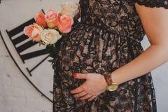 La femme enceinte dans la robe étreint son ventre Photo stock