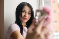 La femme enceinte de charme font le selfie dans la lumière de fenêtre photos stock