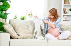 La femme enceinte de femme enceinte prépare des articles d'habillement pour le newb Photo stock