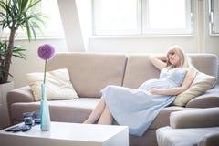La femme enceinte de jeunes apprécient dans sa maison Photos libres de droits