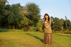 La femme enceinte de jeunes en prévision d'un bébé se tenant en parc rayonne au soleil photo stock