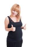 La femme enceinte de jeunes montrant le double aiment ou les pouces- font des gestes Photo libre de droits