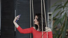 La femme enceinte de jeunes montre son ventre par l'intermédiaire des réseaux sociaux en ligne, utilisant le wifi gratuit dans le clips vidéos