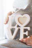 La femme enceinte de jeunes tient l'AMOUR en bois de lettres Concept d'amour Photo stock