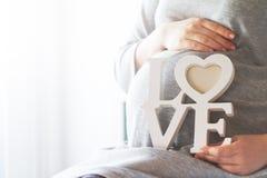 La femme enceinte de jeunes tient l'AMOUR en bois de lettres Concept d'amour Photographie stock libre de droits