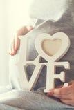 La femme enceinte de jeunes tient l'AMOUR en bois de lettres Concept d'amour Photographie stock