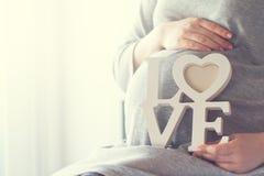 La femme enceinte de jeunes tient l'AMOUR en bois de lettres Concept d'amour Ho Photographie stock libre de droits