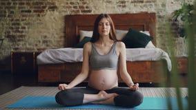 La femme enceinte de jolie brune détend en position de lotus sur le tapis sur le yoga de pratique de hatha de plancher avec des m banque de vidéos