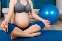 La femme enceinte de plan rapproché médite Images libres de droits