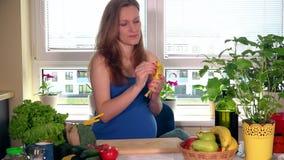 La femme enceinte de sourire affamée avec le grand ventre épluchent la banane dans la cuisine clips vidéos