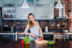 La femme enceinte de sourire dans la cuisine fait cuire la salade végétale Image libre de droits