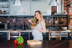 La femme enceinte de sourire dans la cuisine mange de la salade végétale Image libre de droits