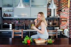 La femme enceinte de sourire dans la cuisine mange des conserves au vinaigre Photographie stock libre de droits