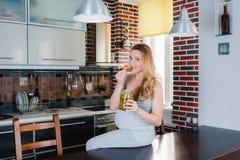 La femme enceinte de sourire dans la cuisine mange des conserves au vinaigre Image stock