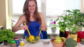 La femme enceinte de sourire versent le sel et mélangent la salade naturelle écologique de légumes clips vidéos