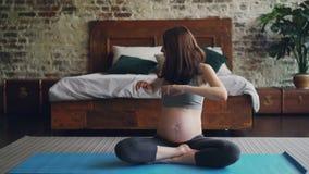 La femme enceinte de femme sportive fait des exercices à la maison se reposant sur le tapis de yoga et apprécier gauche et droit  banque de vidéos