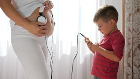 La femme enceinte donne la musique au bébé dans le ventre par des écouteurs, téléphone portable dans des mains de petit garçon se banque de vidéos