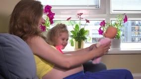 La femme enceinte et la belle fille blonde de fille jouent avec le bébé de jouet - poupée à la maison banque de vidéos