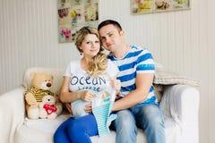 La femme enceinte et le mari de jeunes sur le sofa blanc dans la chambre avec le bébé vêtx Photographie stock libre de droits