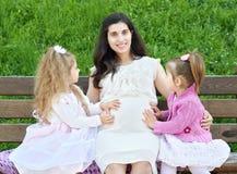 La femme enceinte et les enfants dans la ville d'été garent la famille extérieure et heureuse, le jour ensoleillé lumineux et l'h Image libre de droits
