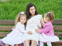 La femme enceinte et les enfants dans la ville d'été garent la famille extérieure et heureuse, le jour ensoleillé lumineux et l'h Images libres de droits