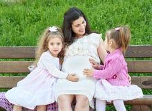 La femme enceinte et les enfants dans la ville d'été garent la famille extérieure et heureuse, le jour ensoleillé lumineux et l'h Photos libres de droits