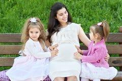 La femme enceinte et les enfants dans la ville d'été garent la famille extérieure et heureuse, le jour ensoleillé lumineux et l'h Photographie stock