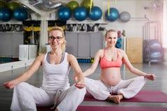 La femme enceinte et son l'entraîneur personnel s'asseyant dans le lotus posent photos libres de droits