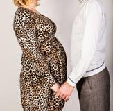 La femme enceinte et son mari beau tiennent des mains Image stock